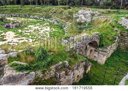 Ruins of Roman Amphitheater in Neapolis Archaeological Park in Syracuse Sicily Island of Italy