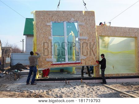 KIEV - UKRAINE APRIL - 19, 2017: Builders Building New Frame House. Installing Frame House Structural Insulated Panel - SIP with Crane Hook. Building SIP House Construction. Insulation House. Unfinished house.