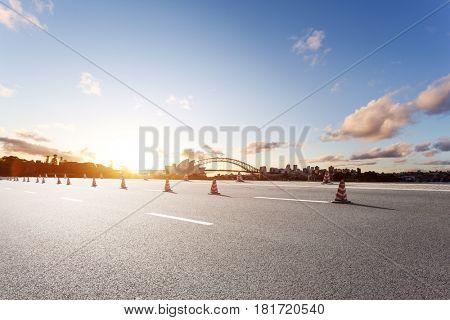 landmark sydney bridge and sydney opera house from empty road at sunrise