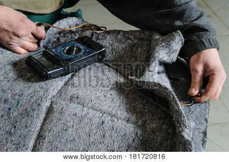 Repair of car seat heating. Car mechanic's hands is using multimeter to check a voltage in cable of heating.