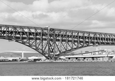 Black and White Minato Bridge cross over Osaka ocean skyline Japan