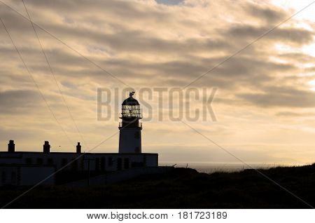 Gorgeous view of a silhouetted Neist Point Lighthouse at sunset in Scotland.
