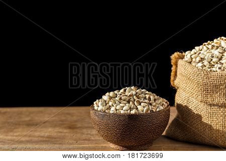 Close Up Millet Rice Or Millet Grains In Bowl On Wooden Table. Isolated On Black