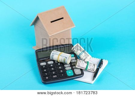 The concept of financial savings to buy a house. Money box three rolls of dollars and calculator isolated on the blue background.