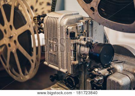 Old vintage metal movie projector with film reel