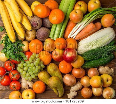 Group Fruits and vegetables on a wooden rustic table, top view: bananas, apples, apples, tomatoes, grapes, pear, onions, celery, beets, potatoes, carrots, cucumbers. Natural healthy food concept