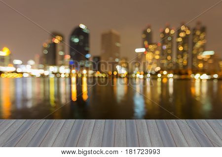 Opening wooden floor Night blurred bokeh light office building with water reflection abstract background