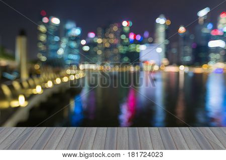 Opening wooden floor Singapore city blurred light nihgt view sea front abstract background