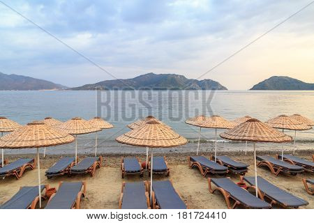 Sunbeds in marmaris beach with mountain view