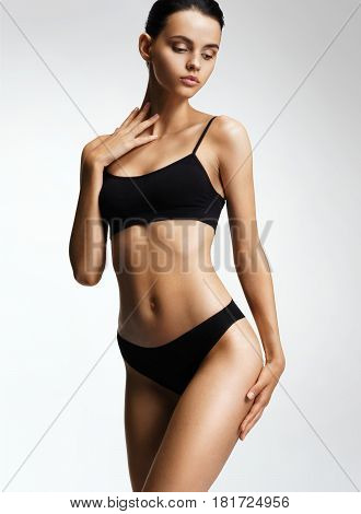 Flawless fashion model in black bikini posing on grey background. Photo of girl with slim toned body. Beauty and body care concept