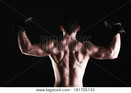 Boxer raising his arms strong athletic muscle man sports guy showing his muscles male back isolated on black background