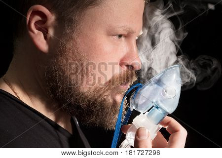 Man breathing through nebulizer mask on black background