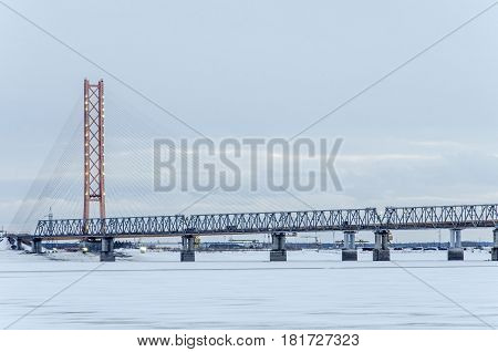 Cable-stayed bridge in winter evening with lights. The biggest bridge in the world with one pylon tower across Ob river in Siberia.