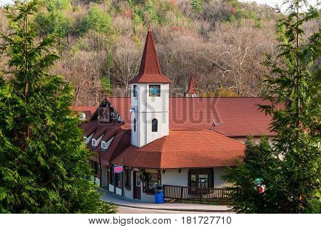 View of the building with the clock tower and mountain through the trees Helen USA