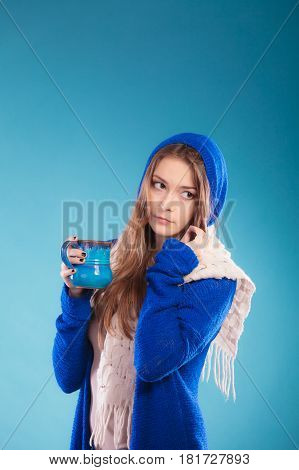 Hot beverage. Closeup teen girl holding blue mug with drink tea or coffee. Woman warming herself