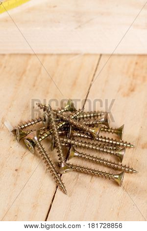Pile Of Metar Screws On The Wooden Planks Background