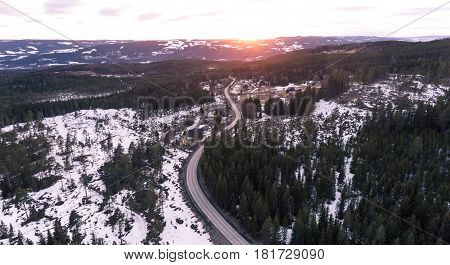 Aerial view of a winding rural road at sunset in Norway