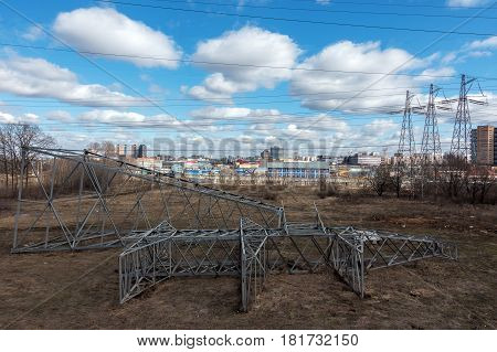 High voltage transmission tower Lies on the ground. Blue sky and cloud background. Industrial landscape