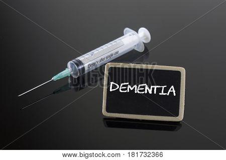 Dementia disease on blackboard and syringe. Health concept