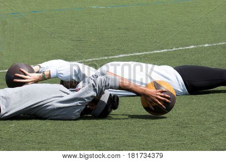 Two high school girls do sit-ups with a medicine ball over their head on a green turf fiels