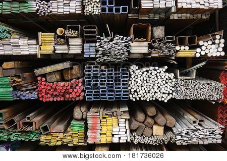 Series of different sizes metal pipes on shelf at market in Asia.