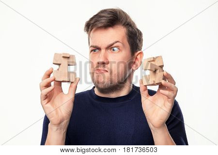 Attractive 25 year old business man looking confused and surprised at wooden puzzle on white studio background.