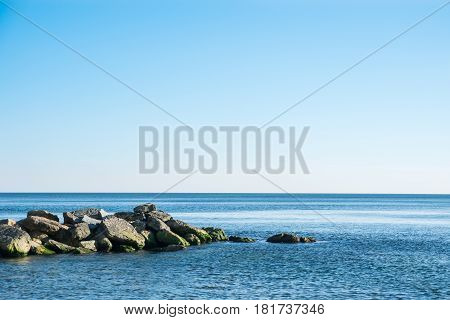 large stones stones in water in a sea with mountains in the background.