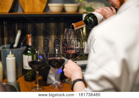 Waiter pouring wine. Skillful sommelier pouring red wine into glass. Woman holding bottle and wineglass standing in cellar.