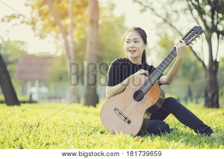 Young attractive woman playing acoustic guitar in the outdoor
