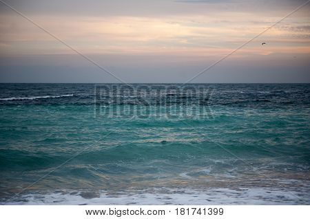 Raging turquoise sea with foaming waves at sunset