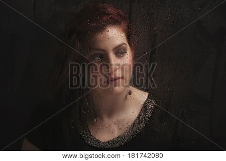 Elegant woman sitting in front of window with rain drops