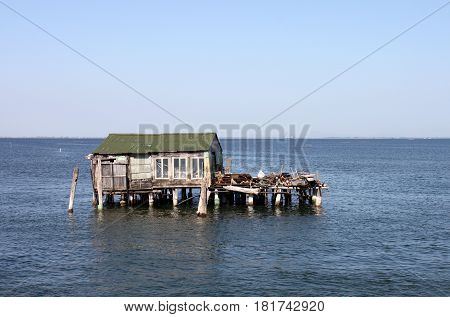 Italy. House of fisher in the water on blue sky background horizontal view