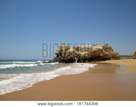 Portugal Algarve Portimao Praia da Rocha. Wave of atlantic ocean sand and rock on blue sky background horizontal view
