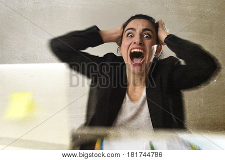 busy attractive woman in business suit working in stress screaming desperate overwhelmed and overworked in office computer desk looking sad and depressed isolated background