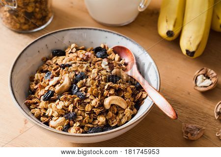 Granola with raisins and nuts in bowl. Breakfast with banana granola on wooden table