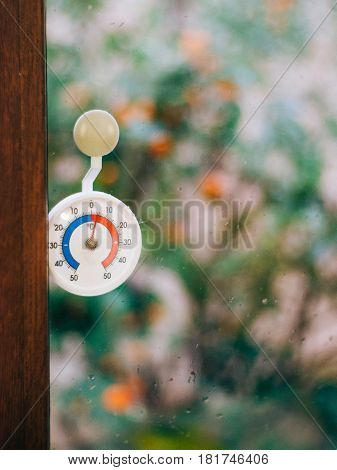 Round thermometer on the window. 5 degrees Celsius. The snow outside the window.