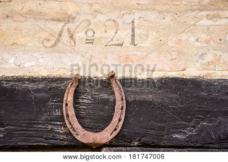 Closeup of house number 21 on the old half-timbered building with horseshoe under the number. It was common to put the horseshoe above the door frame in Europe to bring happiness and prosperity.