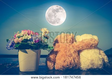 Back view of two doll hugging on table with flowers in vase. Blue sky with full moon background. Concept teddy bears couple with love for valentine day. Greeting or gift card design idea. Vintage tone