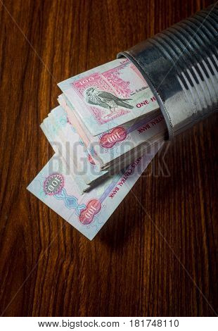 Bundle of Hundred Dirham notes popping out from the tin can. Conceptual image for 'Quick finance' or 'term deposit'.