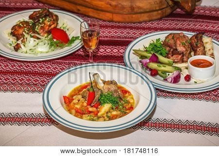 Table served for dinner. Stewed vegetables with beans and pork ribs served with chili pepper and cut dill, grilled pork on flatbread with red onion, pickled cucumbers and plate with roasted quail on background.