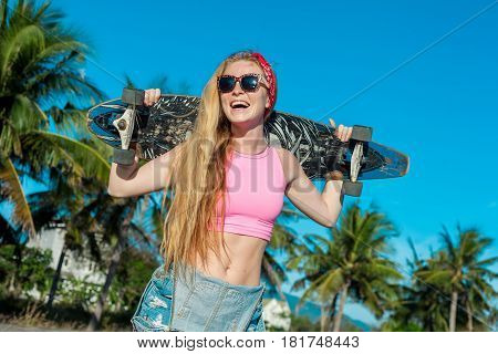Young smiling woman portrait holding long board near palms on the beach. Healthy lifestyle. Extreme sports. Caucasian model with blonde long hair.