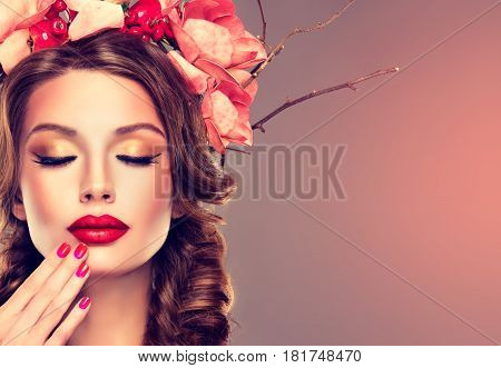 Girl with delicate wreath flowers in hair and  fuchsia red  manicure nail . Hairstyle braid with a wreath and makeup ,red lips and nails.