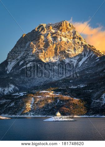 Saint Michel Chapel across Serre Poncon Lake in the Southern French Alps. The sunlit peak of Grand Morgon rises above Saint Michel Bay at sunset after a snow storm.