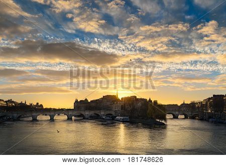 Sunrise and cloud formations over the Seine River in central Paris. The Pont Neuf links Ile de la Cite and the Left and Right Banks. France