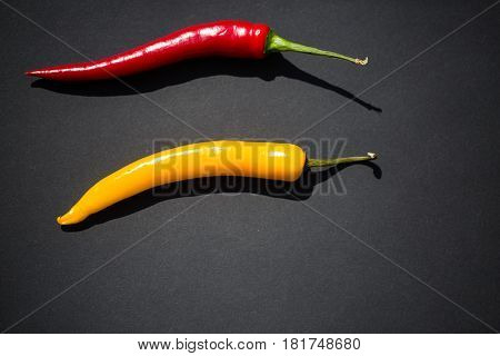 Red and yellow pepperoni on black background