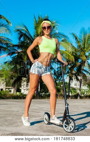 Full length portrait of tanned woman riding a scooter near palms in tropical country. Caucasian model with long hair.