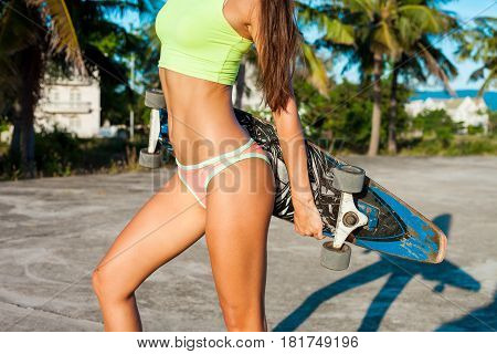 Close-up of body of young tannedwoman standing with longboard. Caucasian model with long hair holdng skateboard near palms in tropical country.