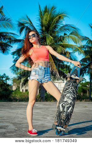 Full length portrait of tanned woman posing with longboard near palms in tropical country. Caucasian model with long hair.
