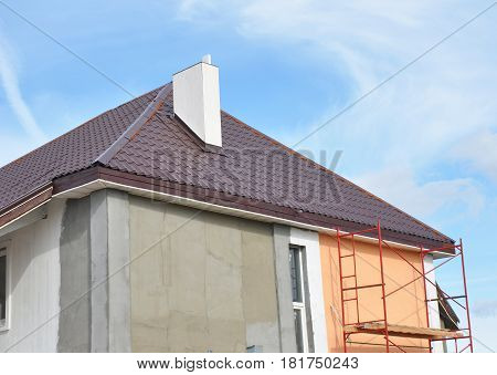 PaintingPlastering Stucco Exterior House Wall. Facade Thermal Insulation and Painting Repair Works During Exterior Renovations. House Roofing Construction Soffits and Roof Insulation Repair. Unfinished house, plastering wall.