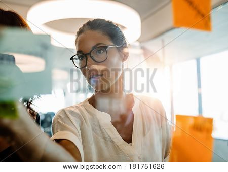 Asian businesswoman looking over a post it note wall and brainstorming. Mature woman standing at the office behind glass wall with sticky notes.